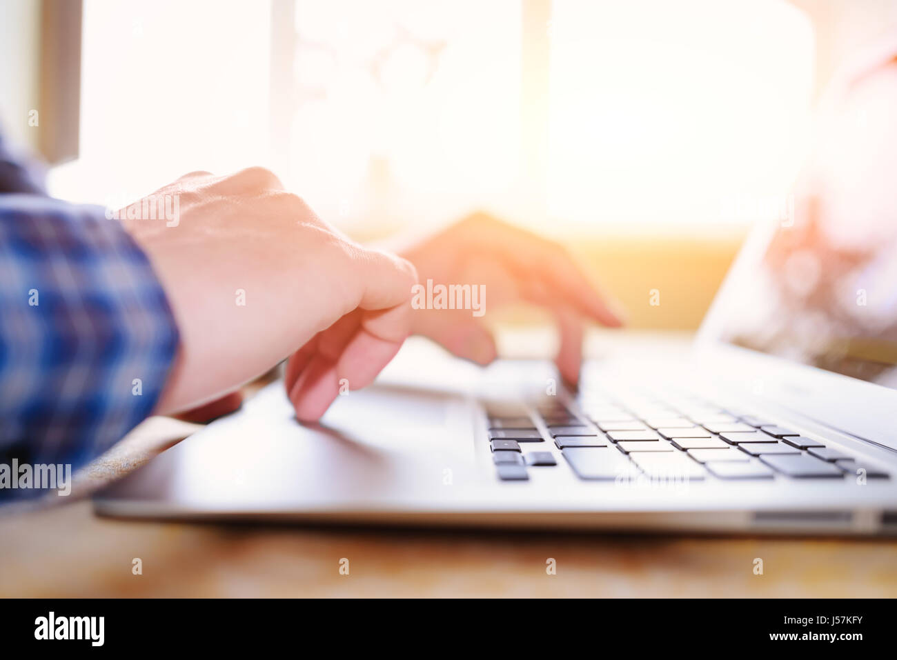 Close-up of a worker using a laptop computer. - Stock Image