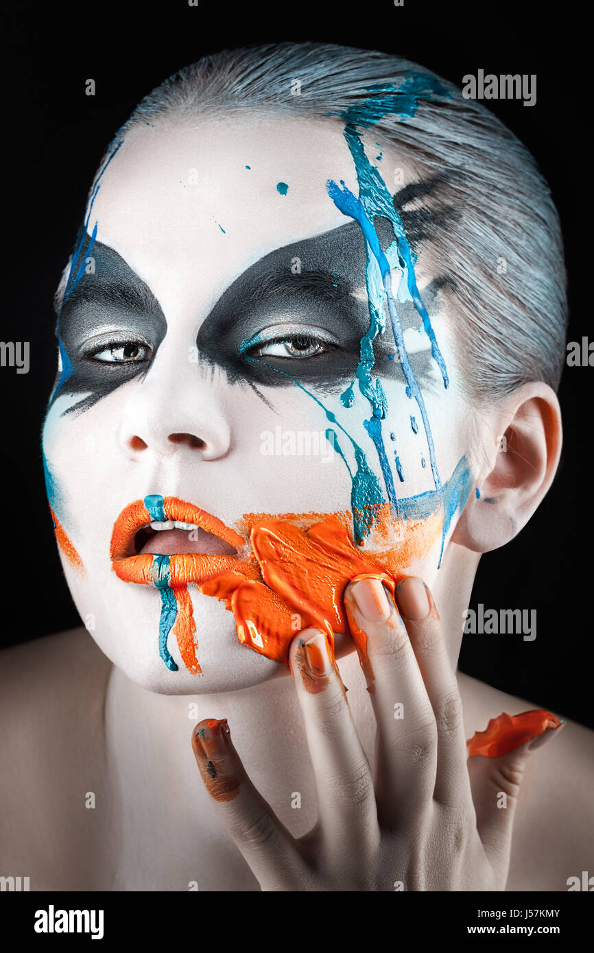 Close portrait of a girl with smeared paint on the face with your fingers. - Stock Image