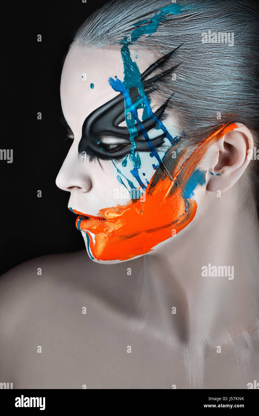 Close portrait of a girl in profile with paint on his face and streaks of paint. - Stock Image