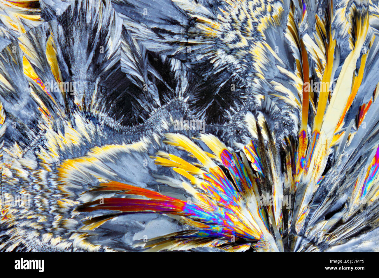 Microscopic view of colorful sucrose crystals. Recrystallized table sugar. Polarized light, crossed polarizers. - Stock Image