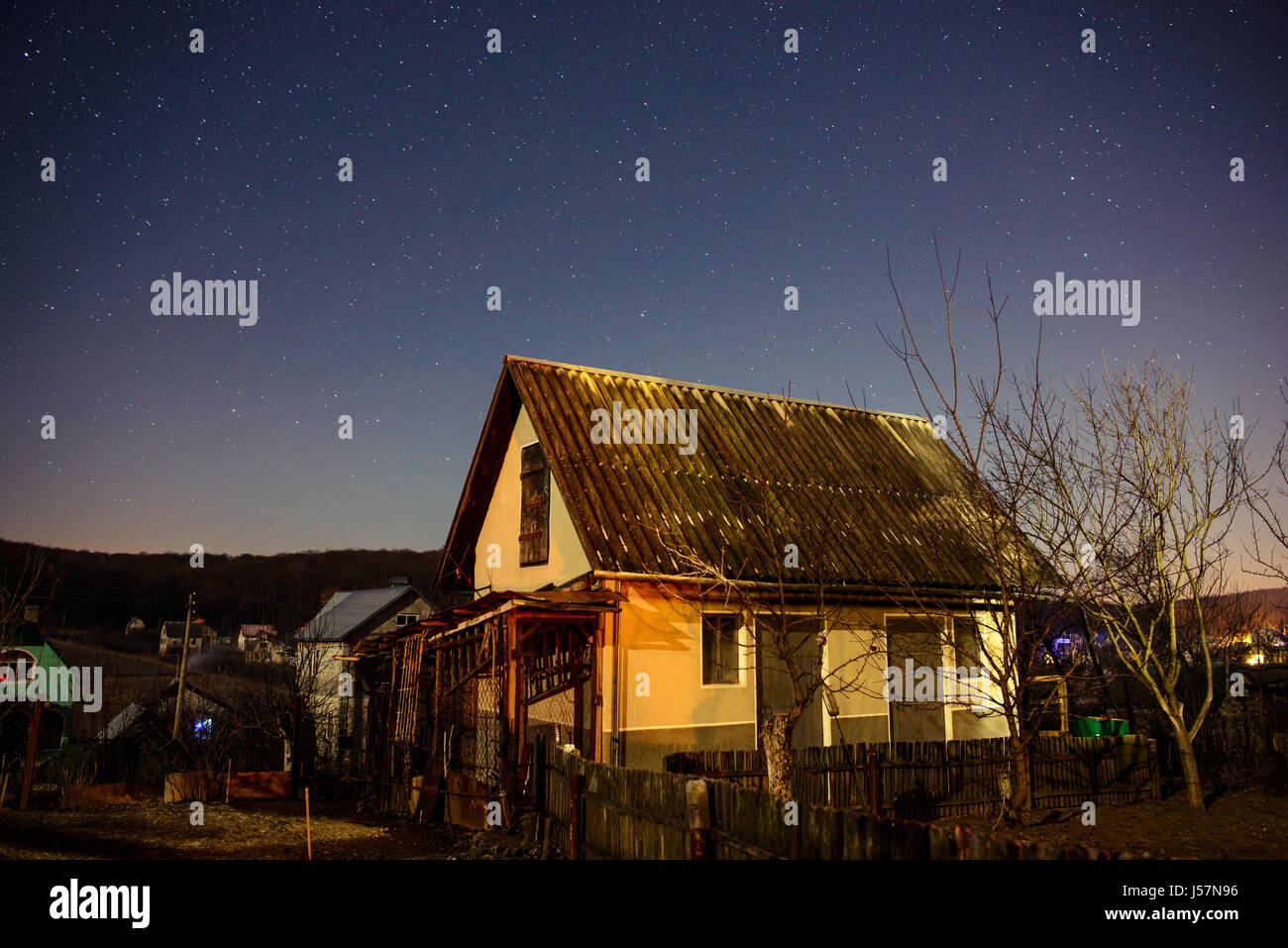 wooden house on a background of the night sky. - Stock Image
