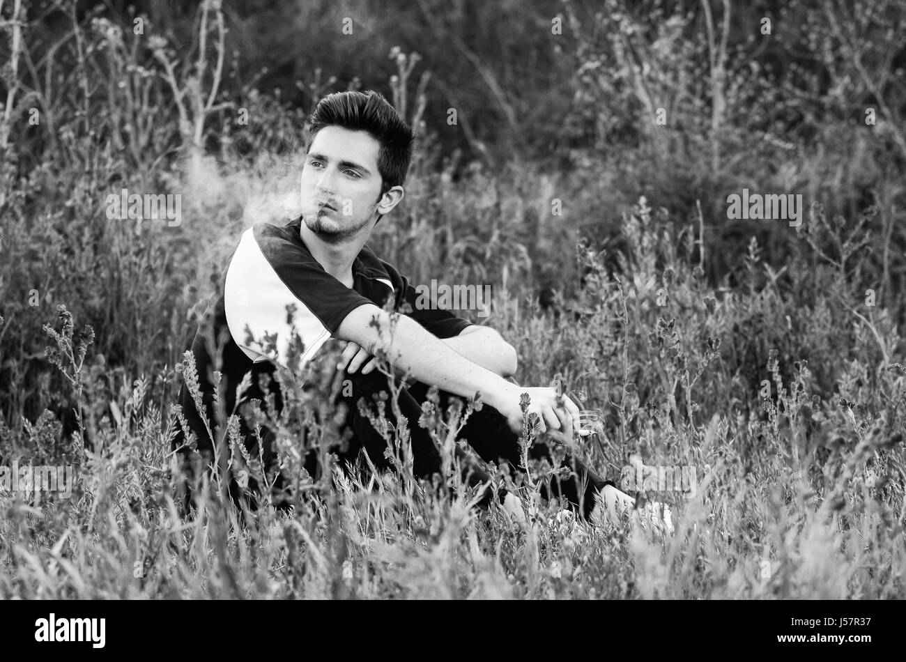 black and white portrait of lonely man smokong a cigarette in a field - Stock Image