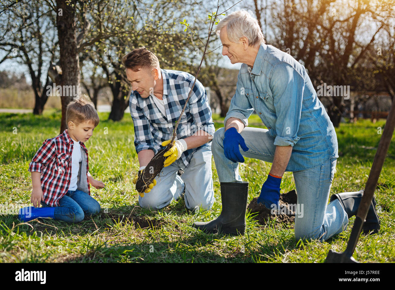 Older family members teaching kid how to care about nature - Stock Image
