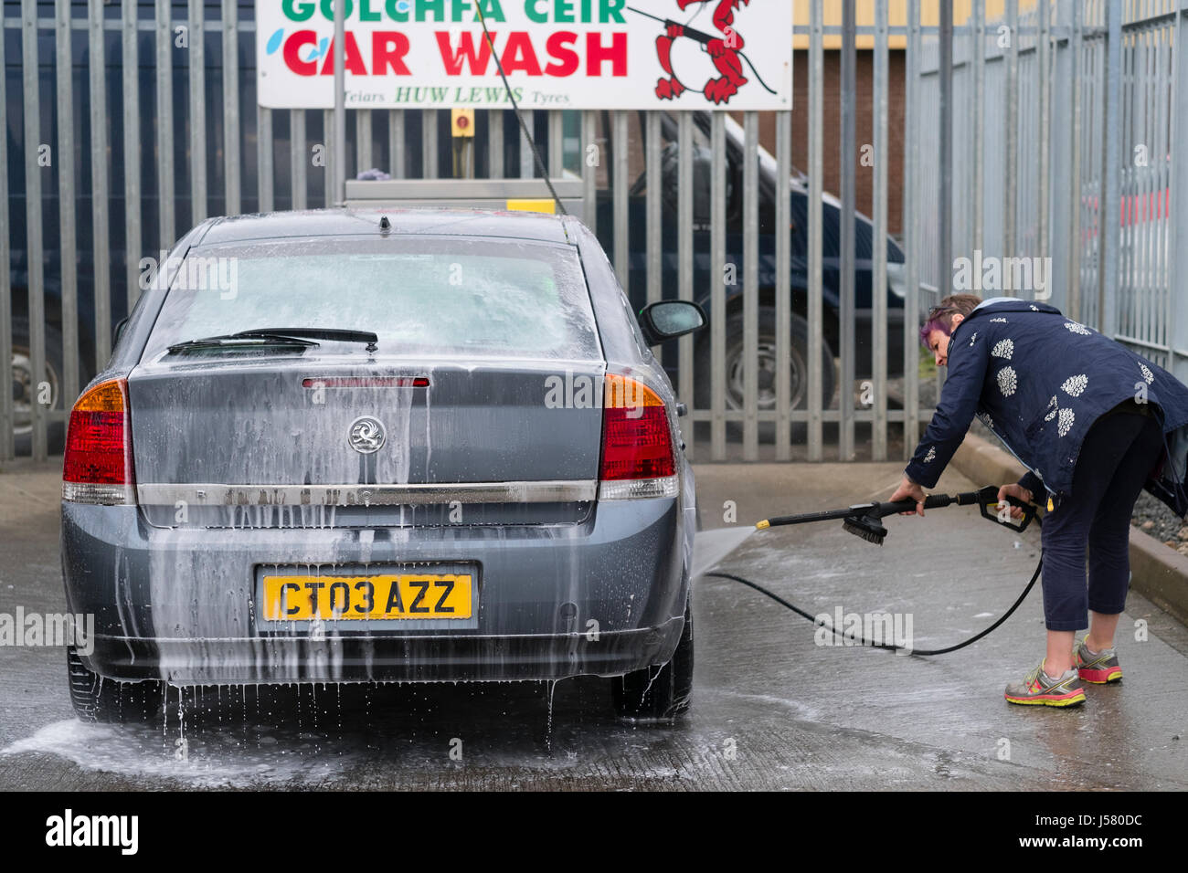 A middle aged woman power washing cleaning her saloon car at