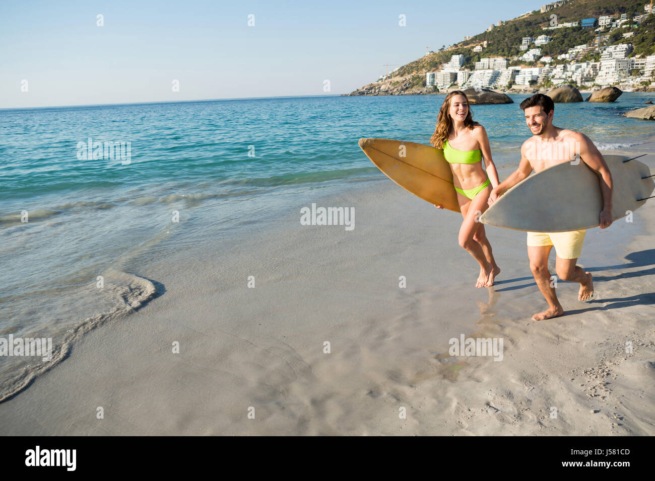 Happy couple running together while holding surfboards at beach on sunny day - Stock Image