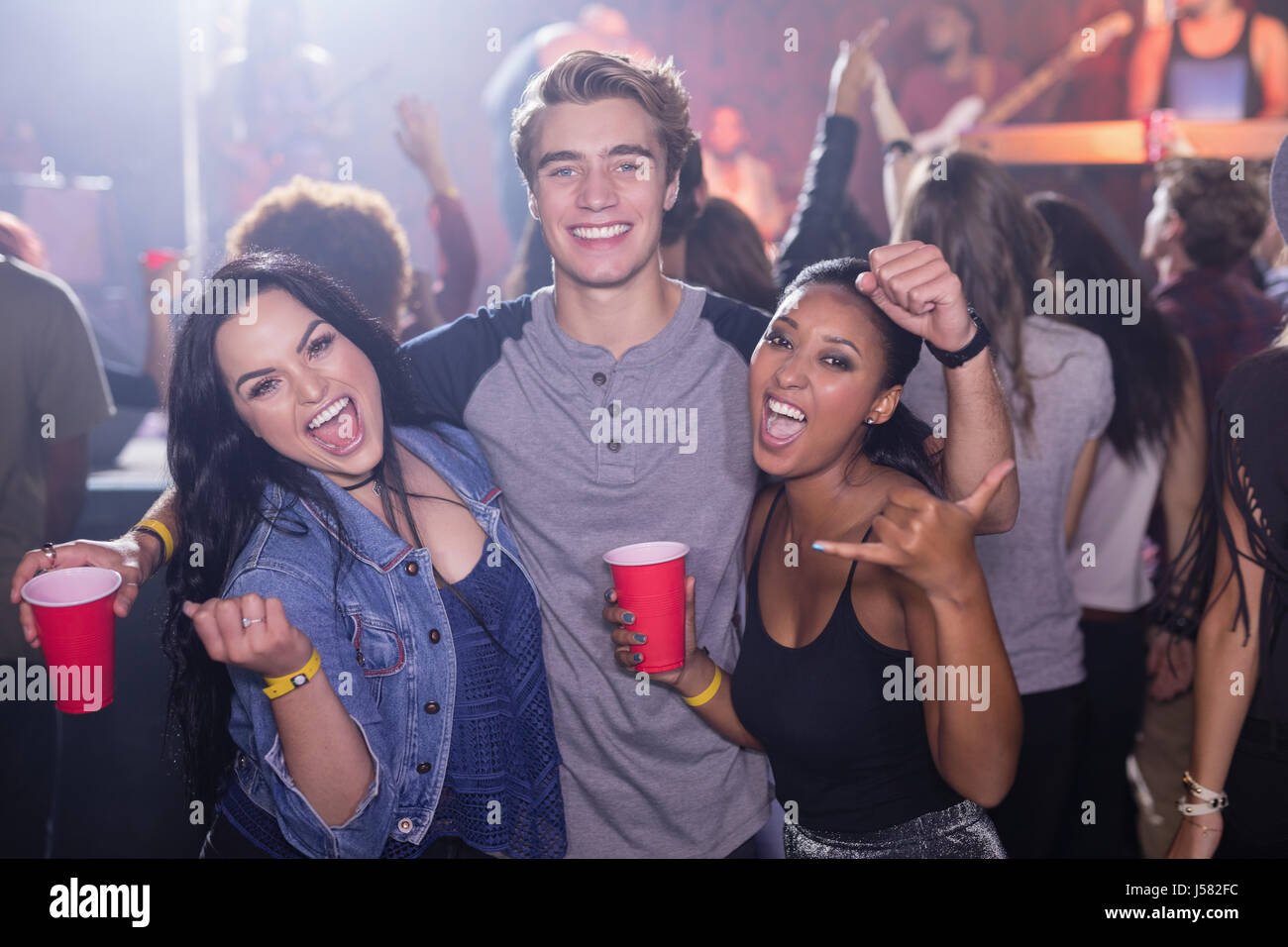 Portrait of cheerful friends holding disposable cups while standing at nightclub - Stock Image