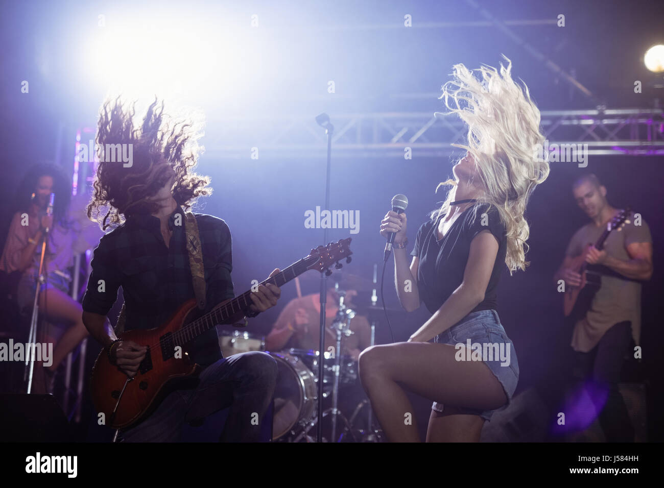 Female singer and male guitarist with tousled hair performing together on stage at nightclub - Stock Image