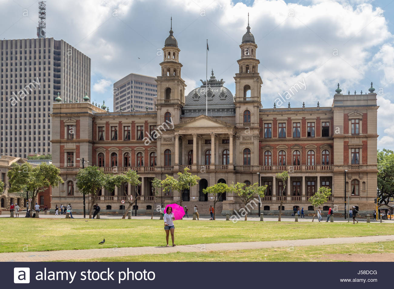 A woman carrying a bright purple sunshade walks across the grass in front of the Palace of Justice, Church Square, - Stock Image