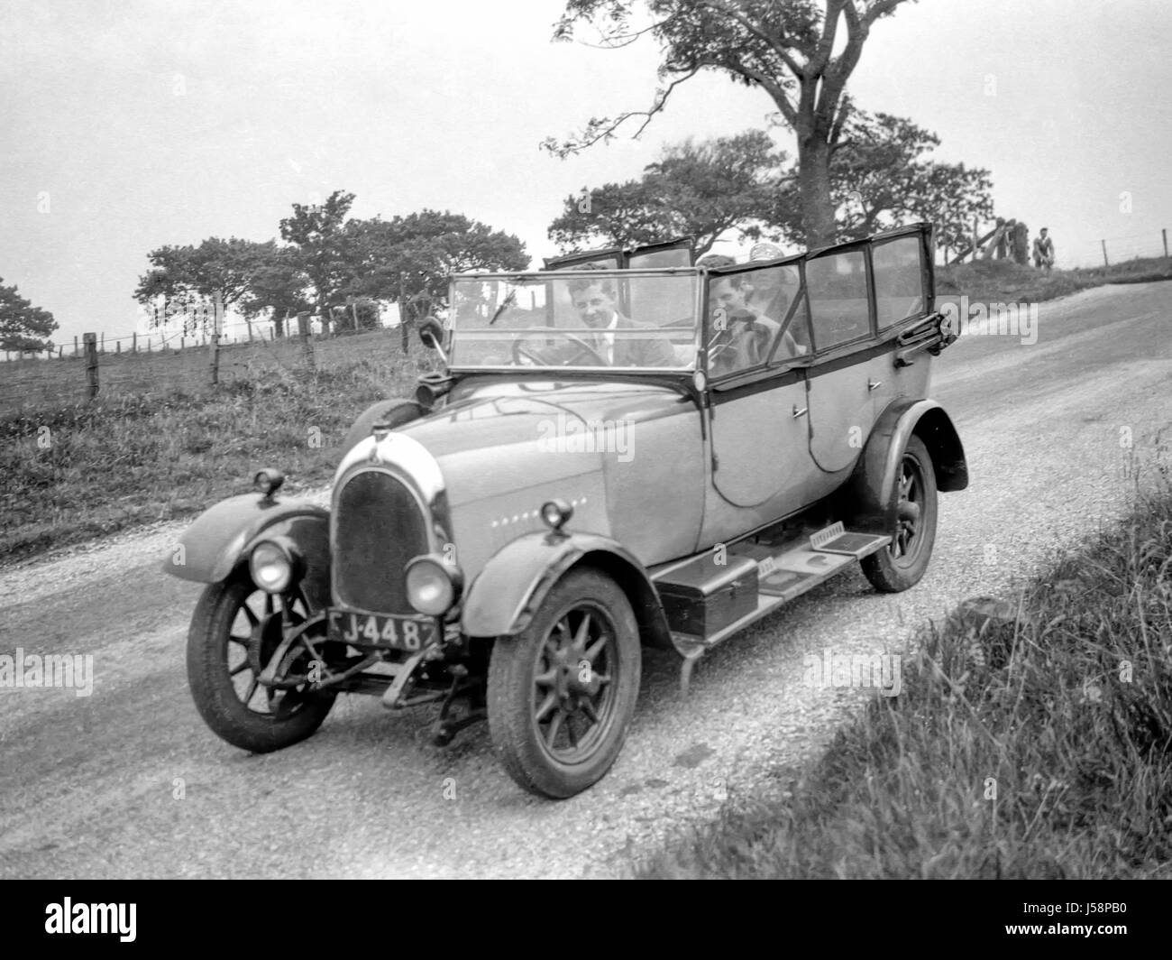 A group of people out for a drive in a 11.9hp Bean four door convertible car built in 1926 and first registered - Stock Image
