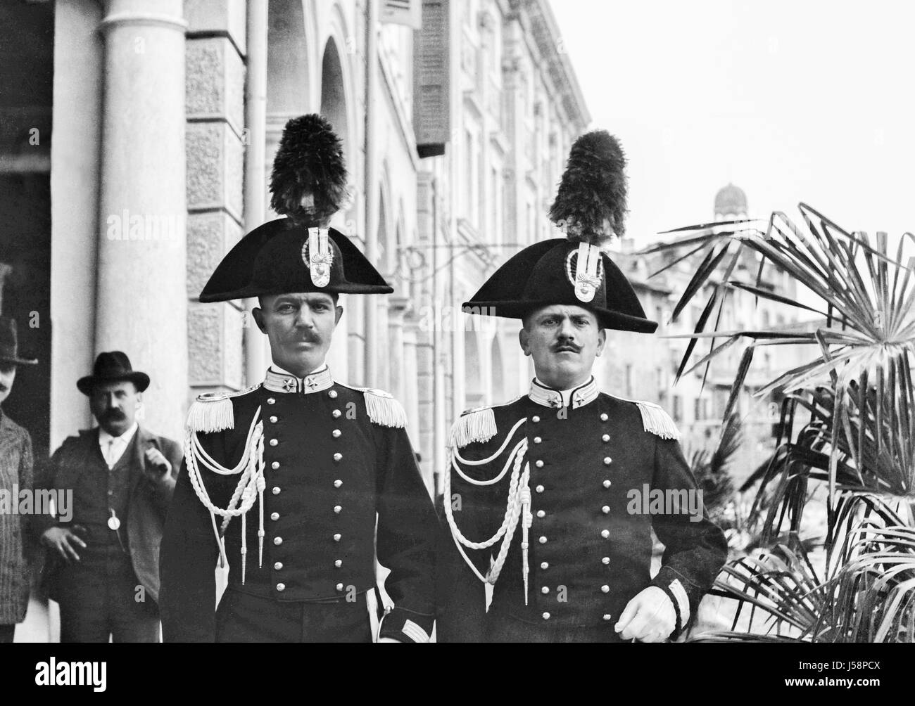 Two Italian Carabinieri in full dress uniform pose for the camera on a city street. in 1900. Restored from a high - Stock Image