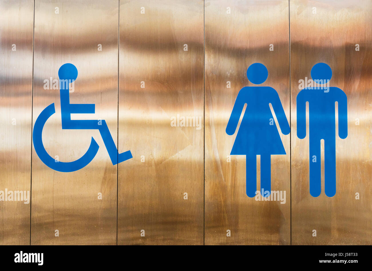 Sign outside toilet indicating facilities for the disabled, for women and for men. - Stock Image