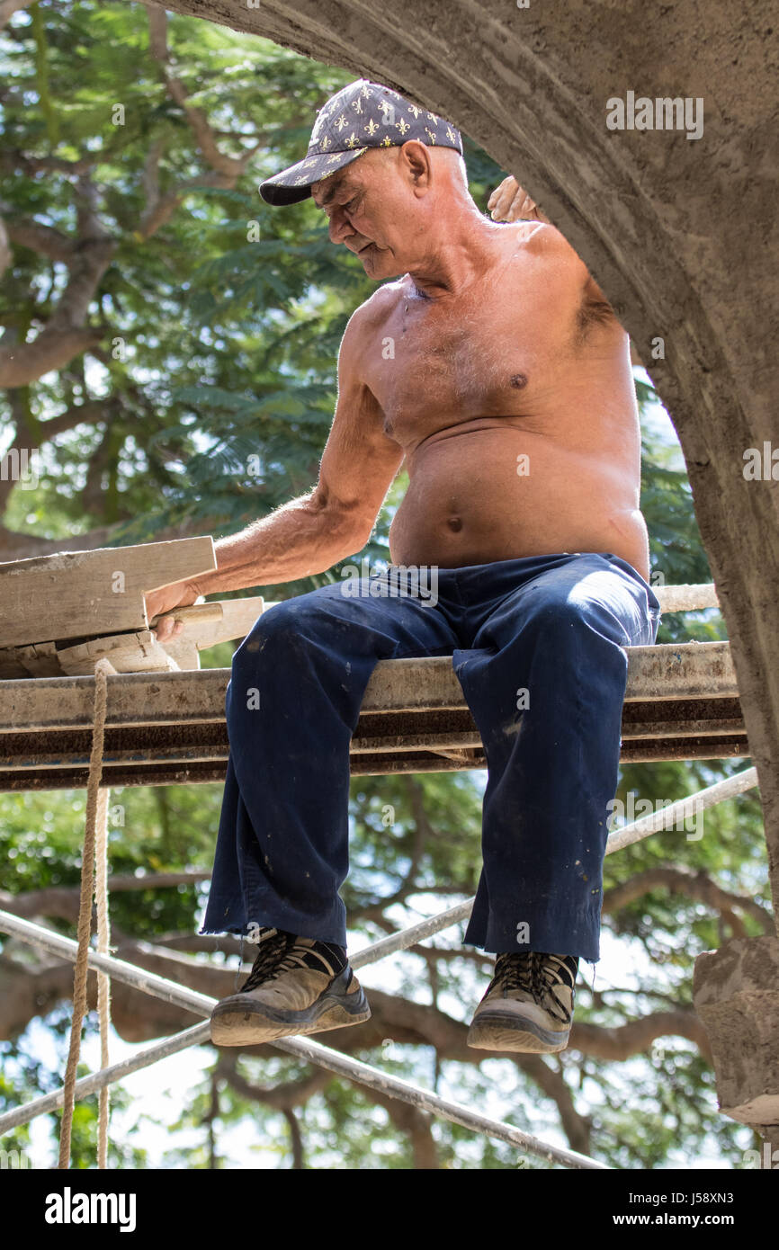 Shirtless plasterer working on an old sugar plantation in Cuba - Stock Image