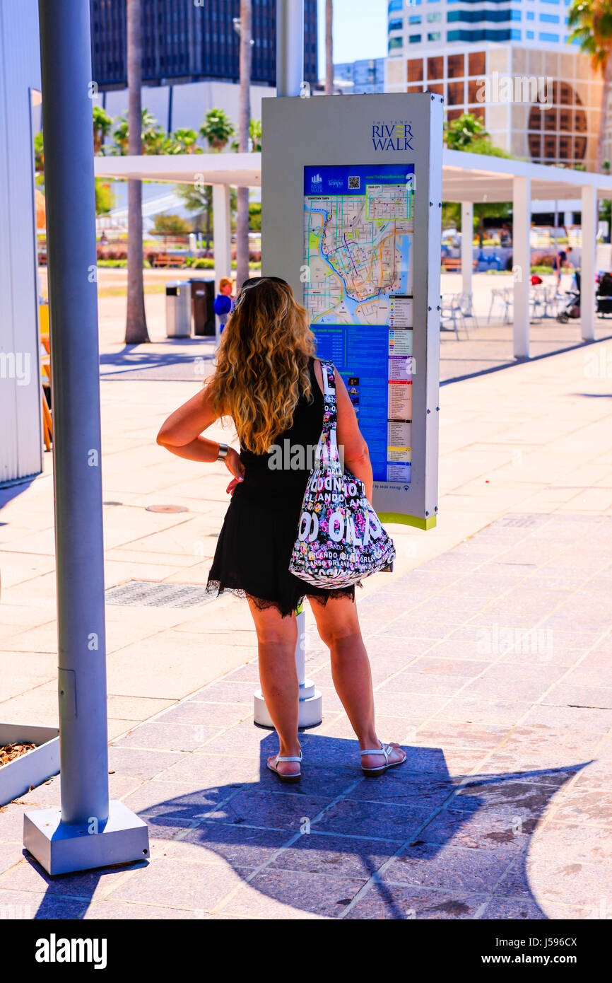 Woman reviews the information baord on the Riverwalk in downtown Tampa FL - Stock Image