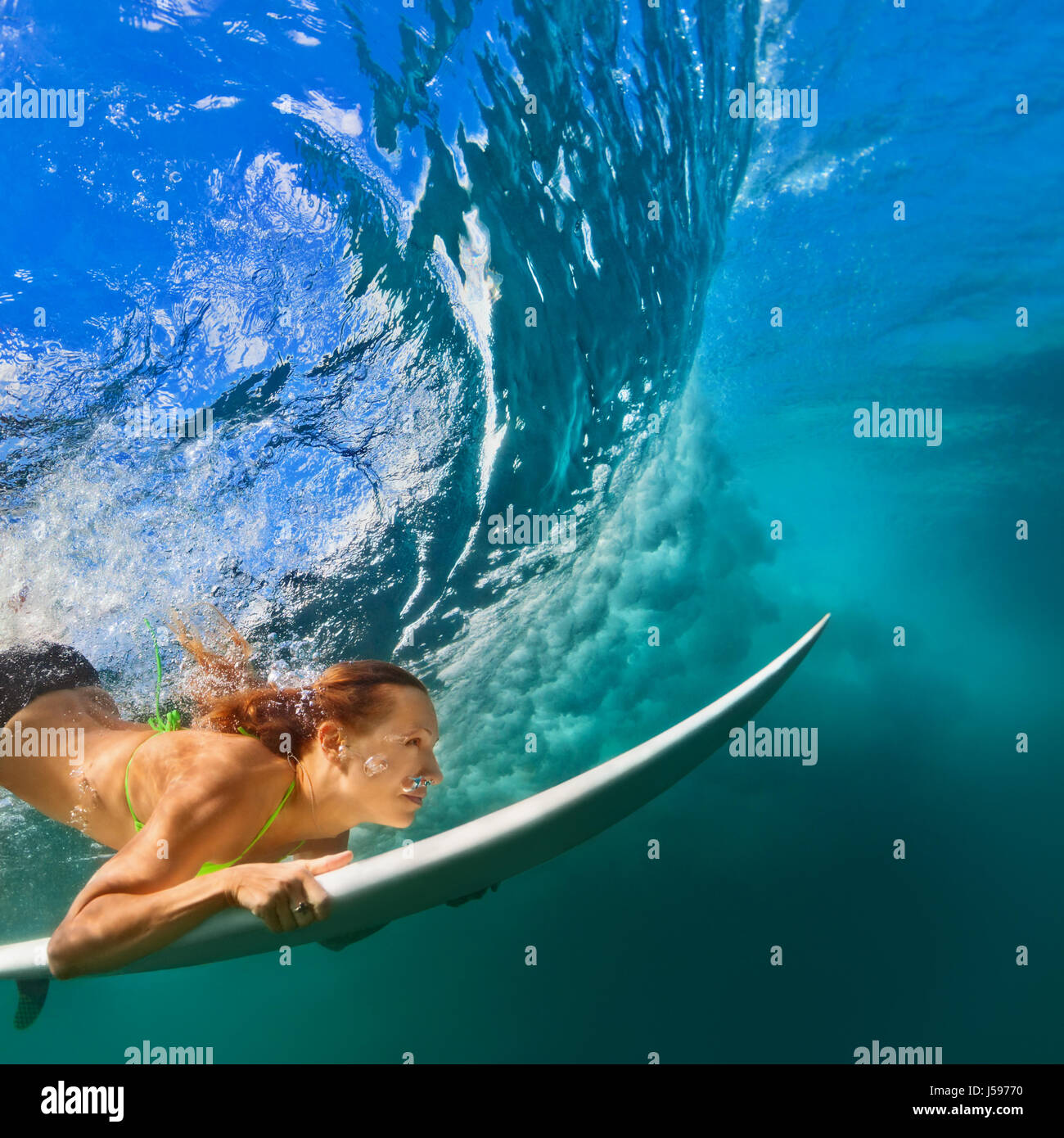 Active girl in bikini in action. Surfer woman with surf board dive underwater under breaking big wave. Healthy lifestyle. - Stock Image