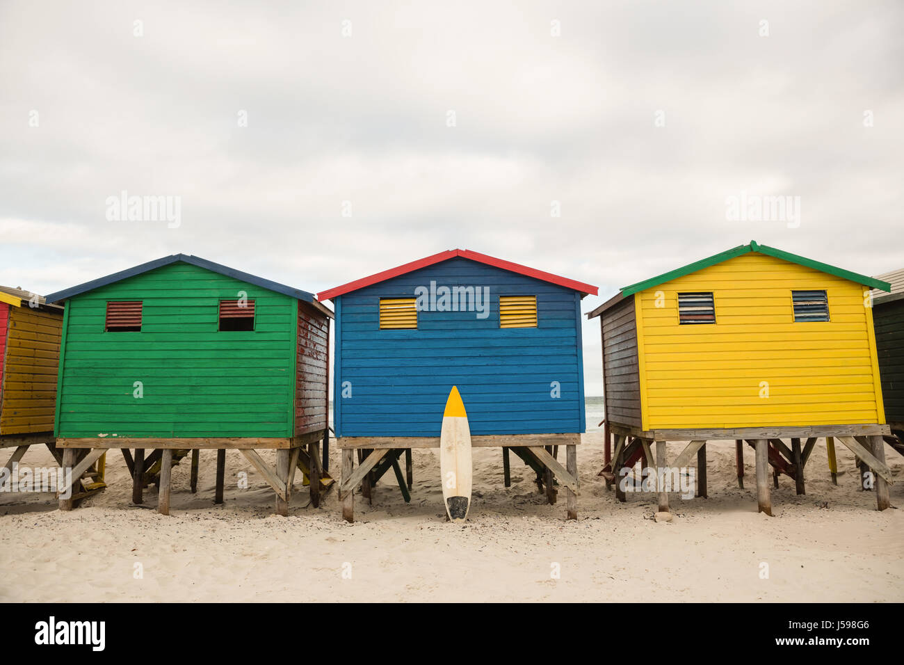 Multi colored wooden huts on sand at beach - Stock Image