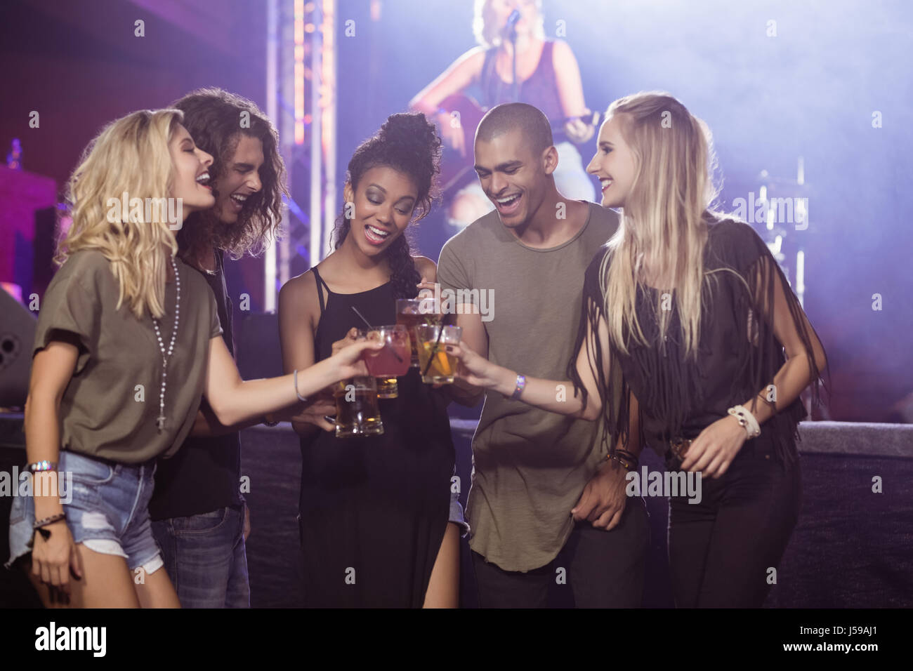 Happy friends toasting beer glasses with performer singing in background at nightclub Stock Photo