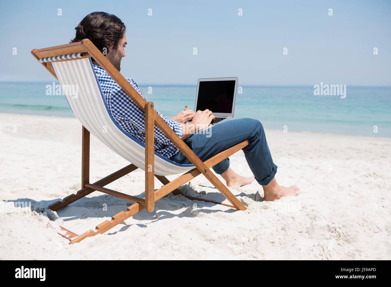 Side View Of Man Using Laptop While Sitting On Deck Chair At Beach Stock Photo Alamy