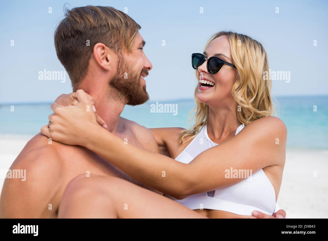 Happy man carrying girlfriend while standing at beach - Stock Image