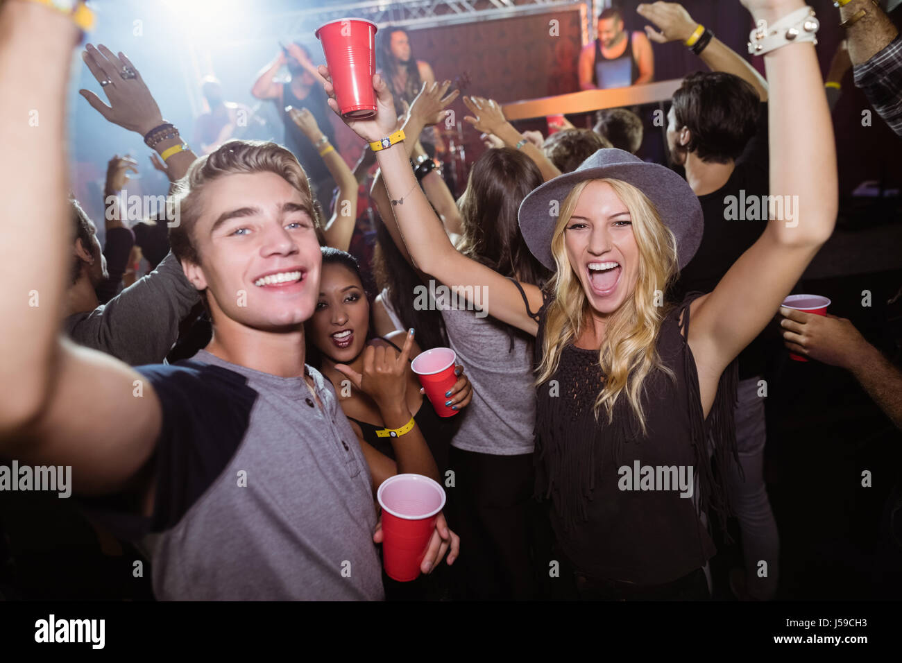 Portrait of friends with disposable cups dancing in nightclub - Stock Image