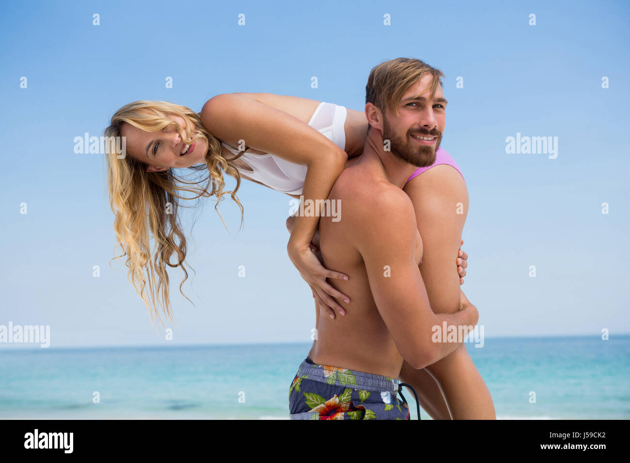 Portrait of man carrying girlfriend while standing at beach against clear sky - Stock Image