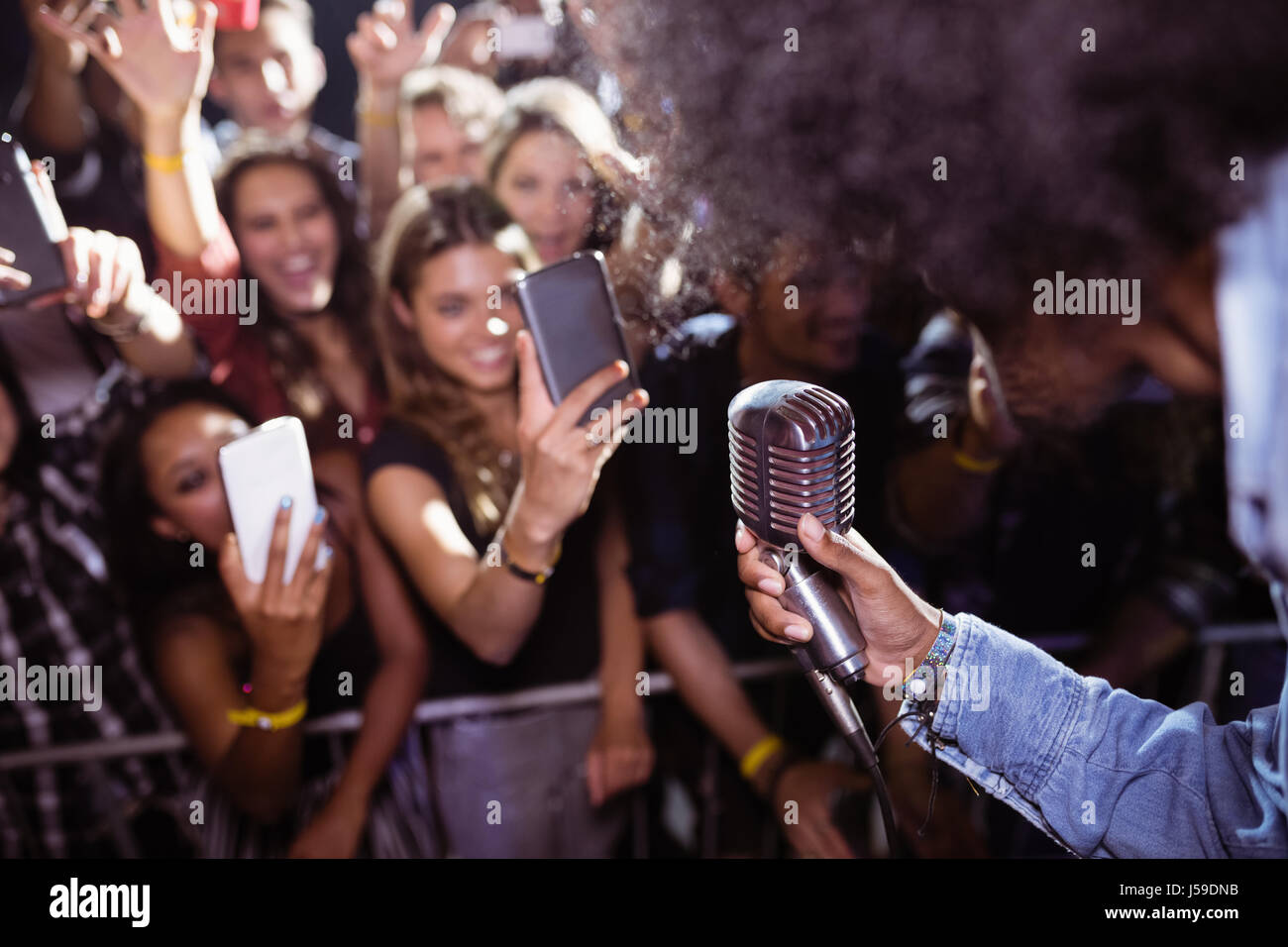 Fans photographing singer performing at nightclub during music festival - Stock Image