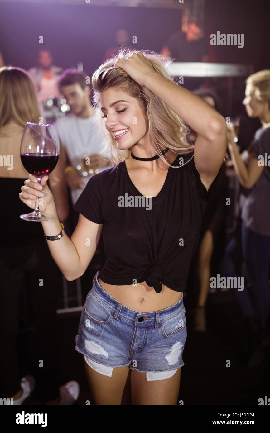 Smiling young woman with eyes closed holding wineglass while dancing at nightclub Stock Photo