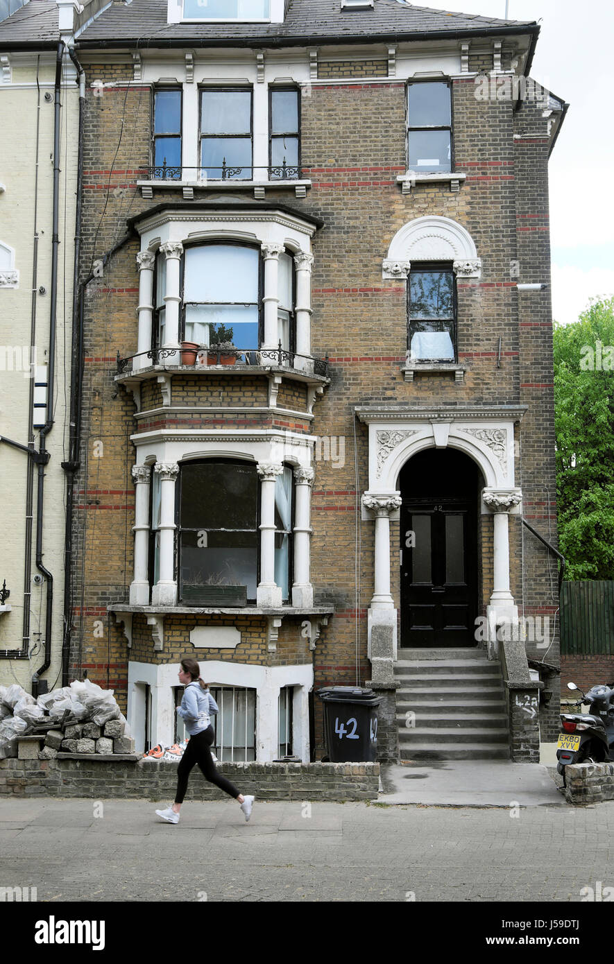 A female jogger running past a run down house in the area of Newington Green, London N5 UK  KATHY DEWITT - Stock Image