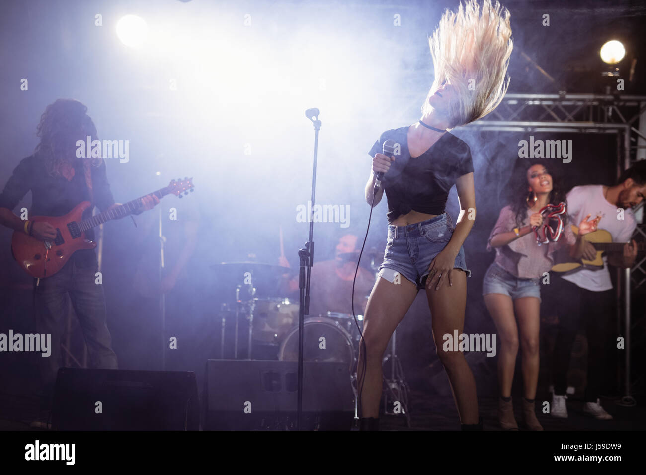 Young singer with tousled long hair performing on stage at nightclub - Stock Image