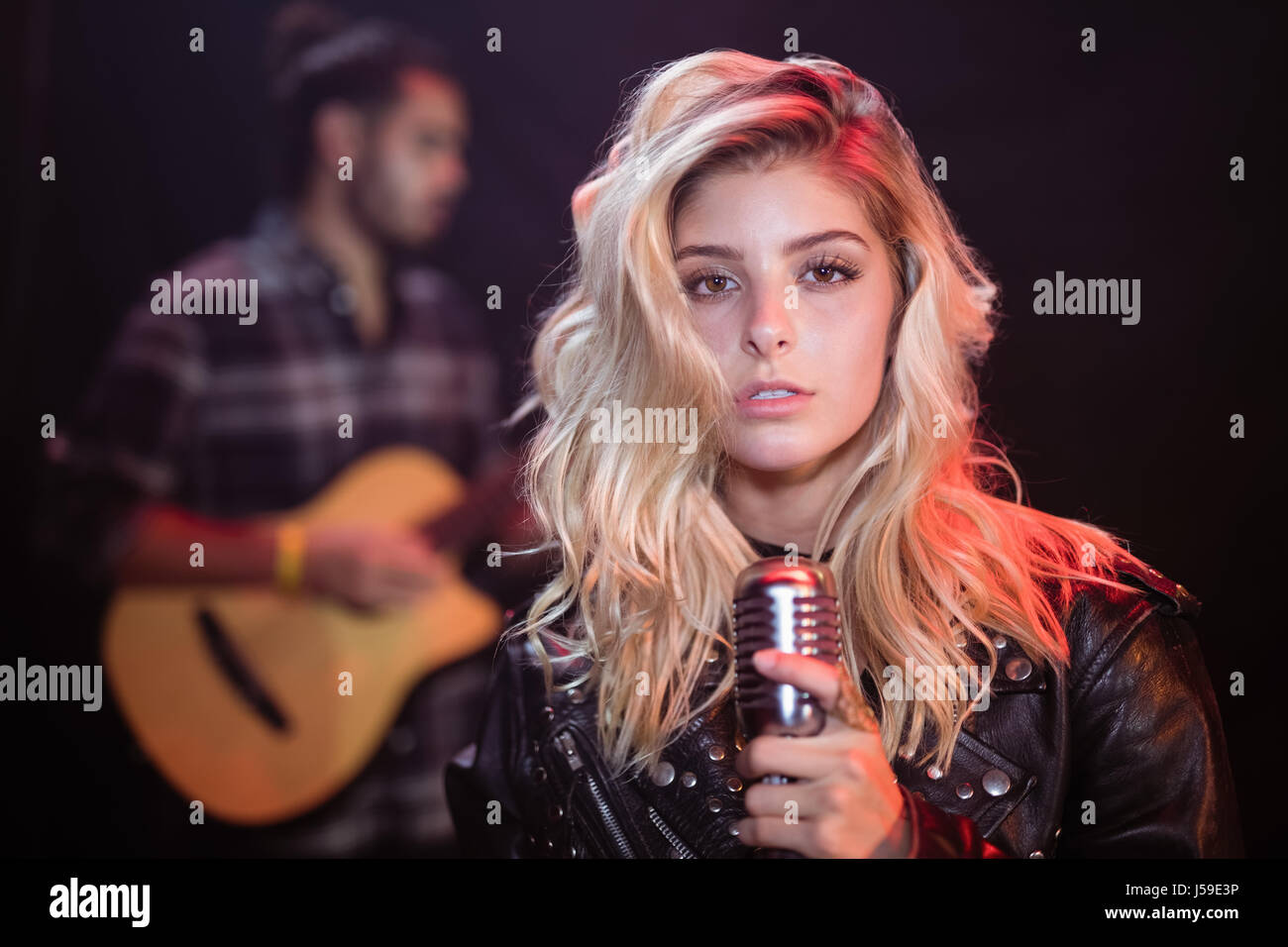 Portrait of young female singer holding mic at nightclub during music festival - Stock Image