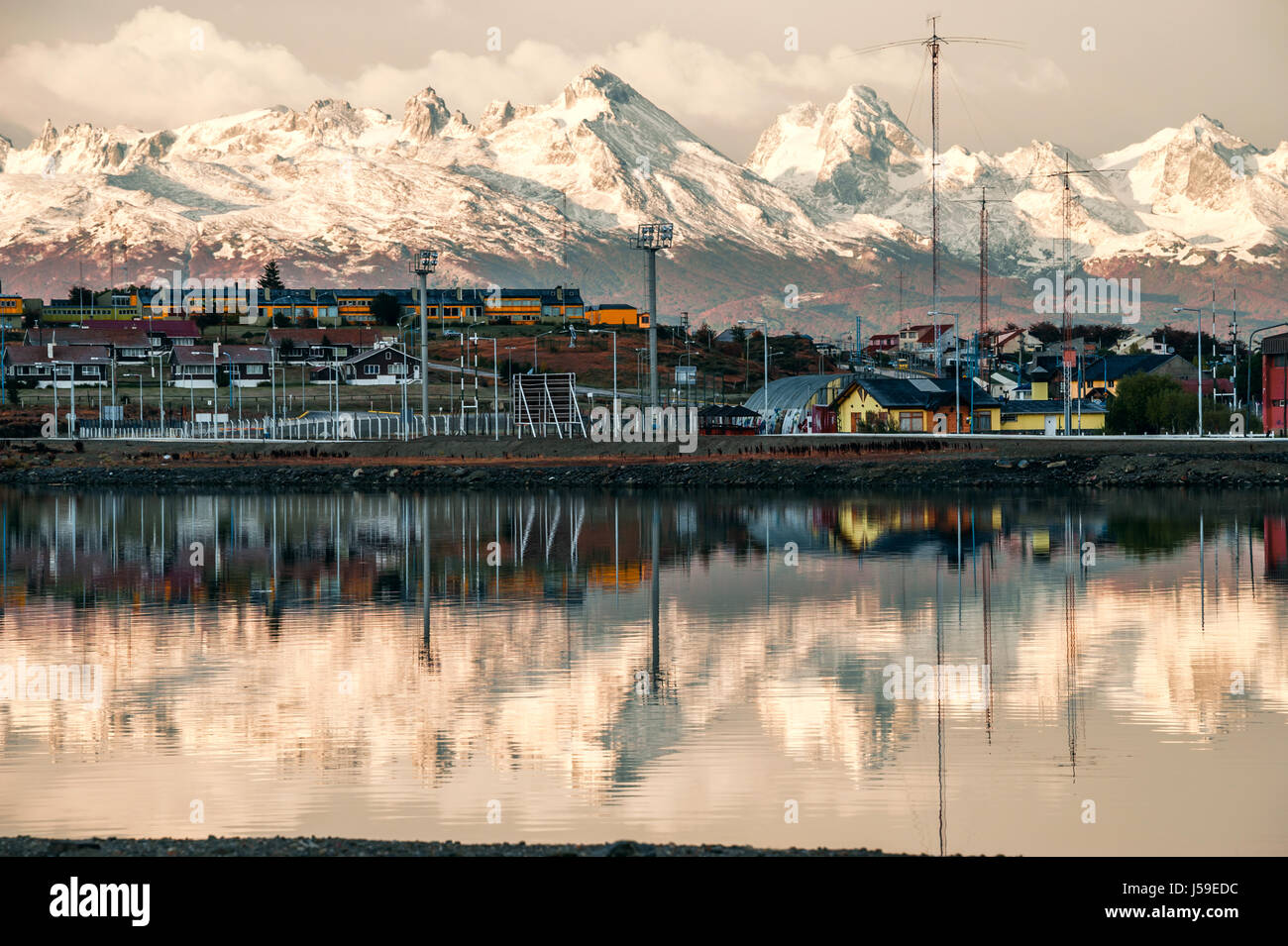 Reflection of the most southern city of Argentina in serene morning water of the Beagle Channel. Ushuaia is the - Stock Image