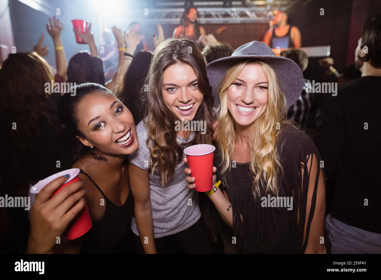 Portrait of female friends with disposable cups enjoying music in nightclub - Stock Image