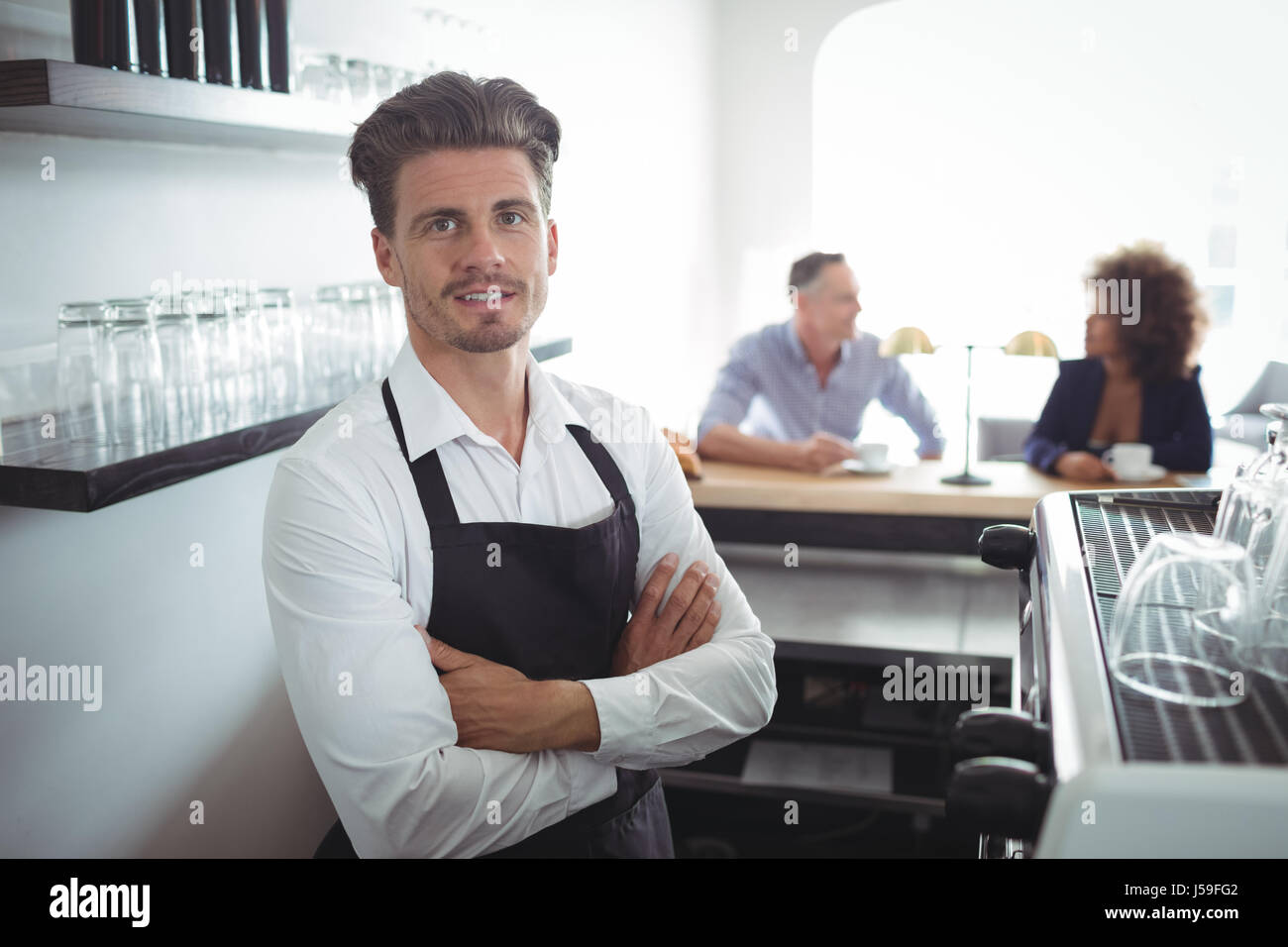 Portrait of waiter standing with arms crossed at counter in restaurant - Stock Image