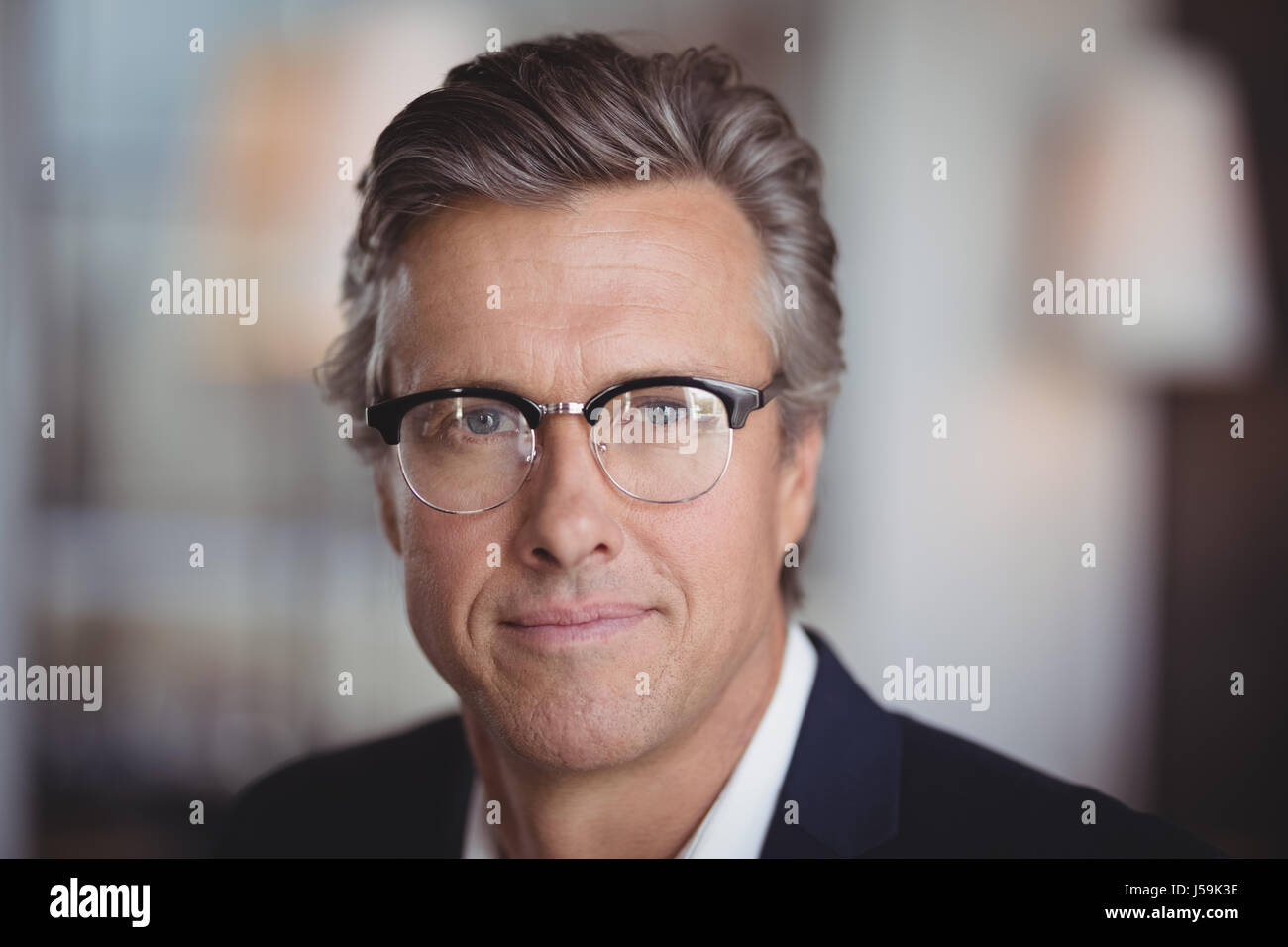 Portrait of smiling businessman in spectacle at restaurant - Stock Image