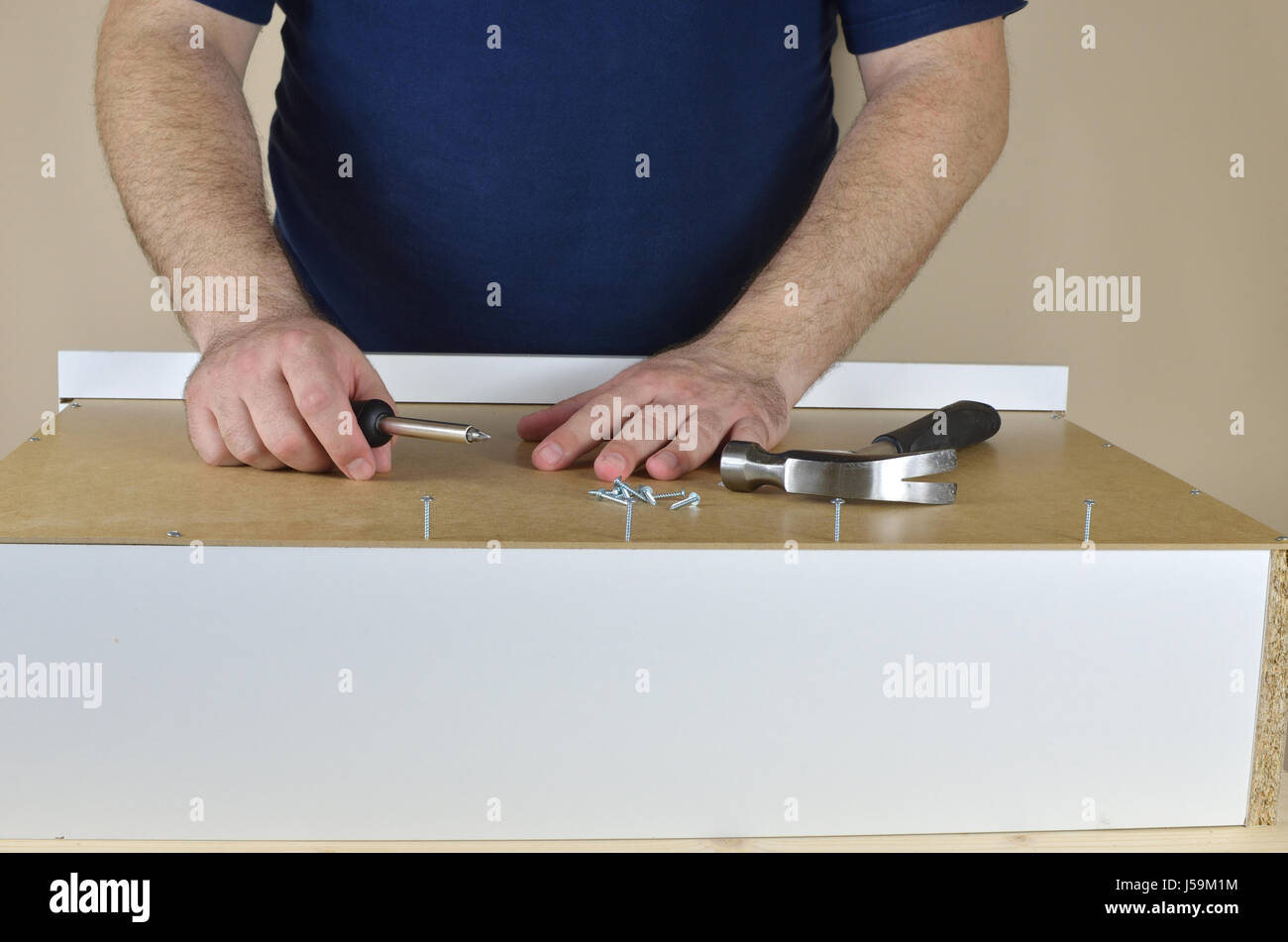 Man's hands on a drawer backside set on working table - Stock Image