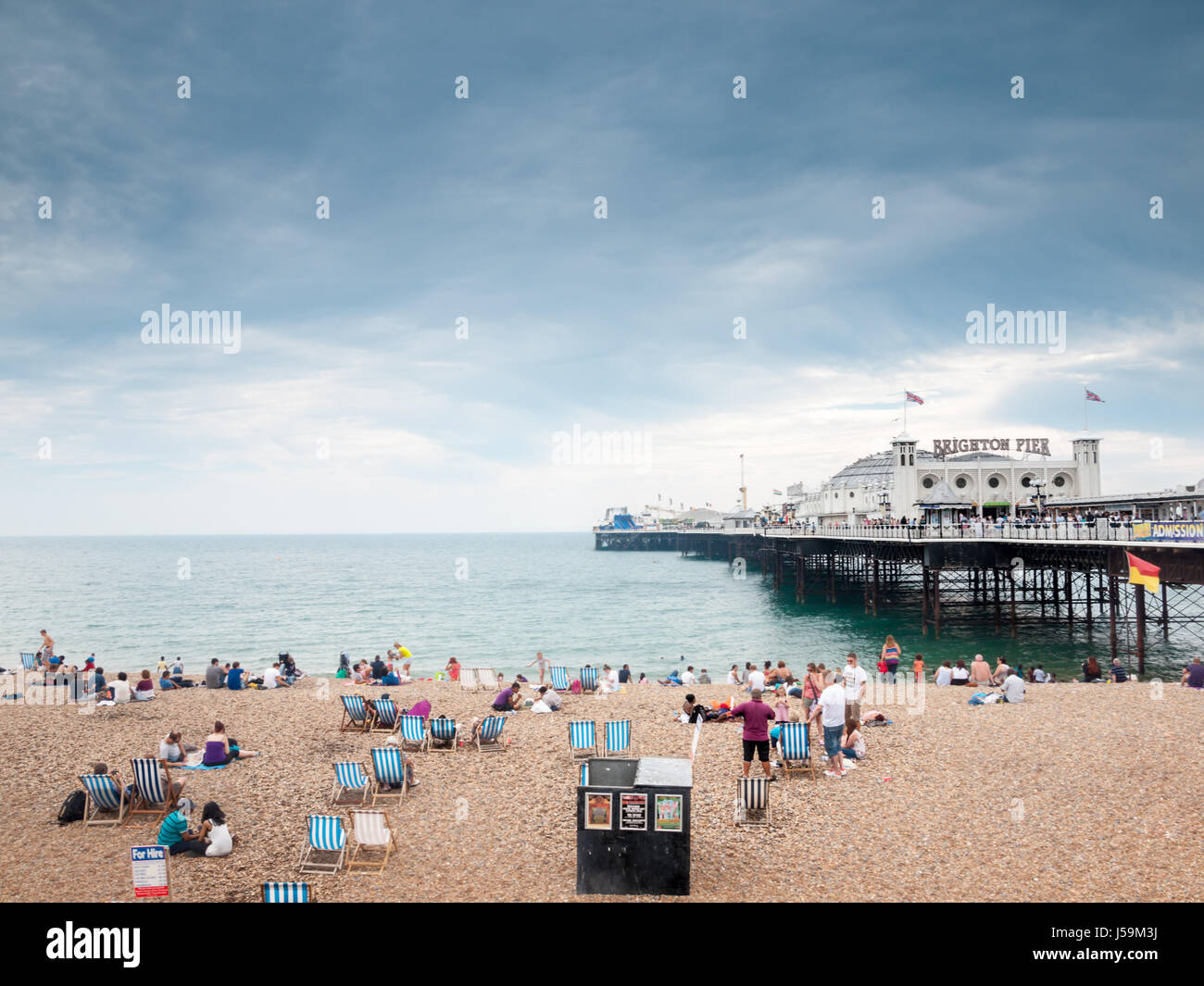 Holidaymakers on Brighton Beach and Pier - Stock Image