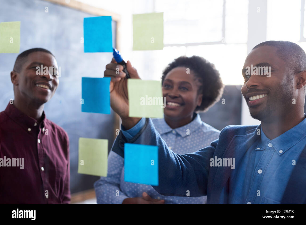Positive African work colleagues brainstorming together in an office - Stock Image