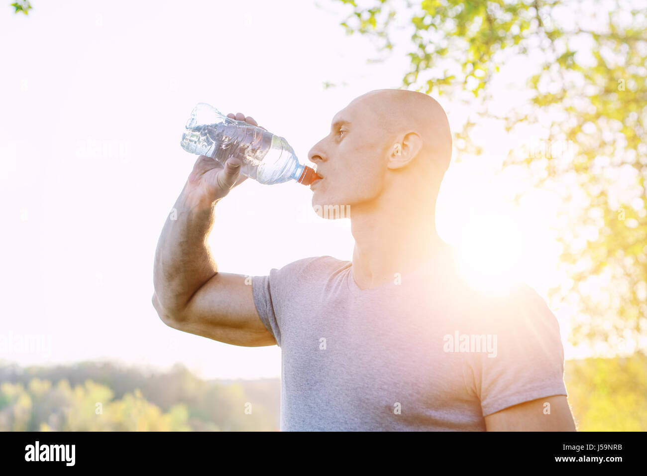 young athlete is refreshing himself with water, sport and healthy lifestyle - Stock Image
