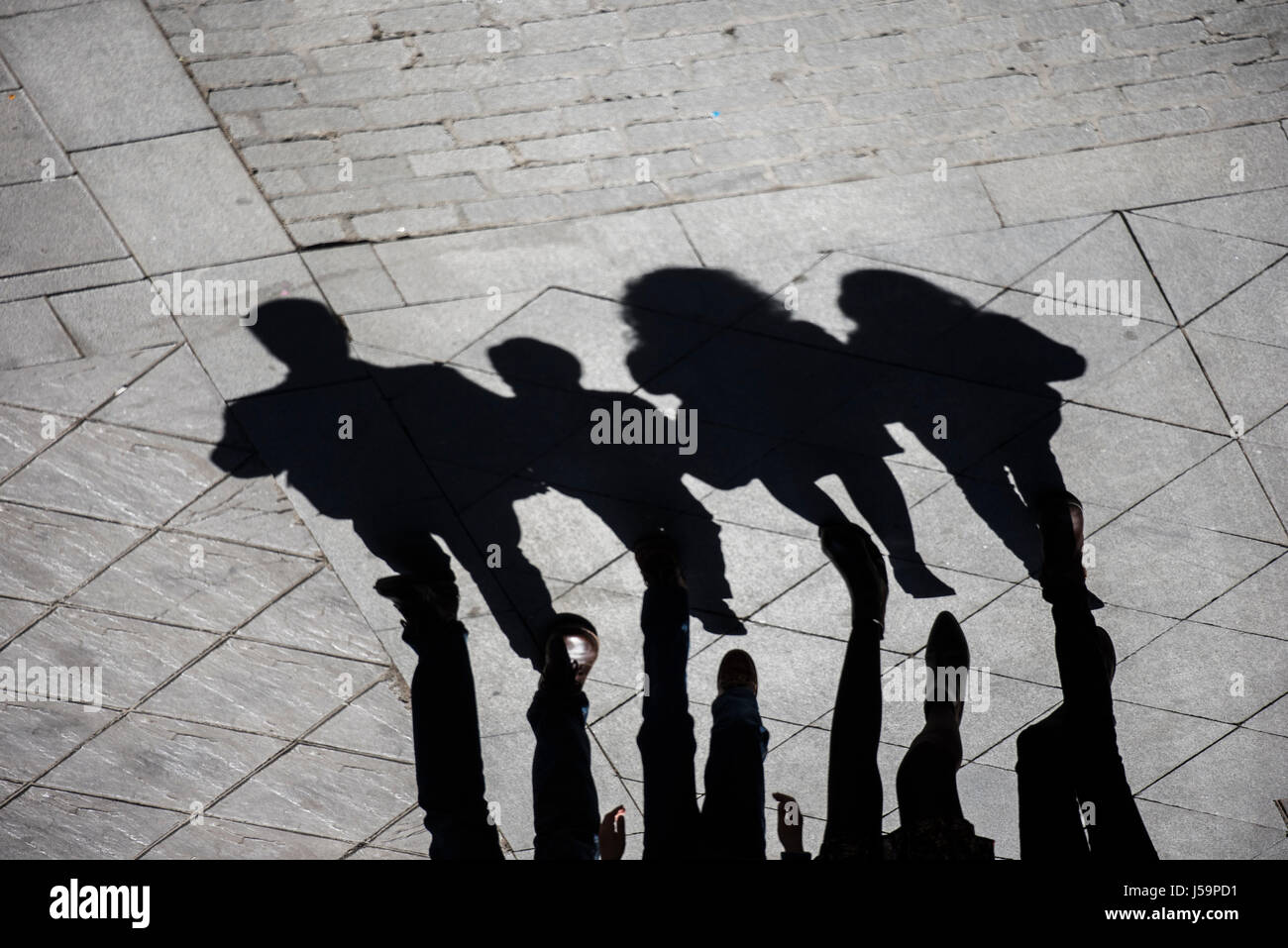 The shadows and silhouettes of a family group (father, mother, son and daughter) walking down the street - Stock Image