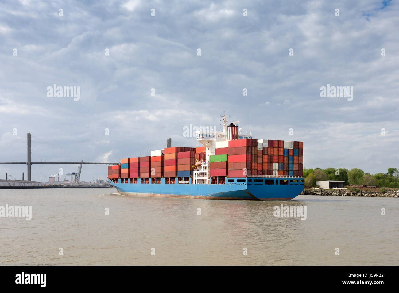 Fully loaded cargo container ship approaching the Talmadge Memorial Bridge as it enters Port of Savannah in Georgia. - Stock Image