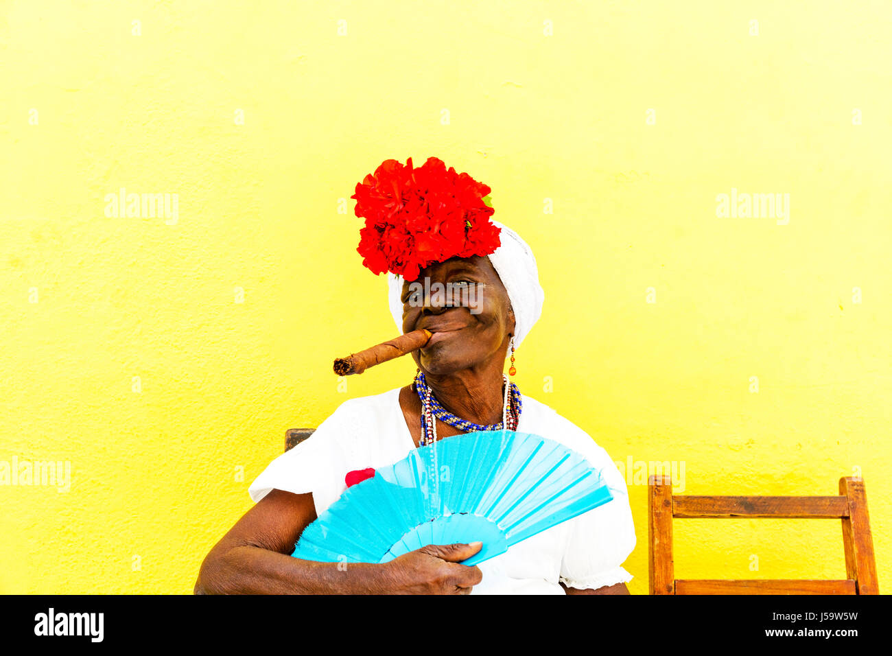 Cuban woman with cigar in mouth posing for tourists earning money for photos Cuba Havana woman cigar posing with - Stock Image