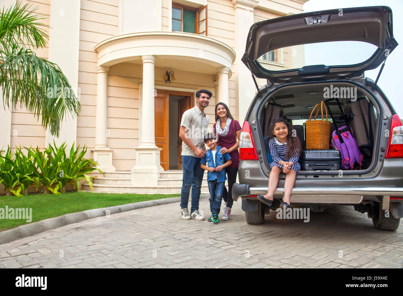 Family standing beside open boot of parked car to go on vacation - Stock Image