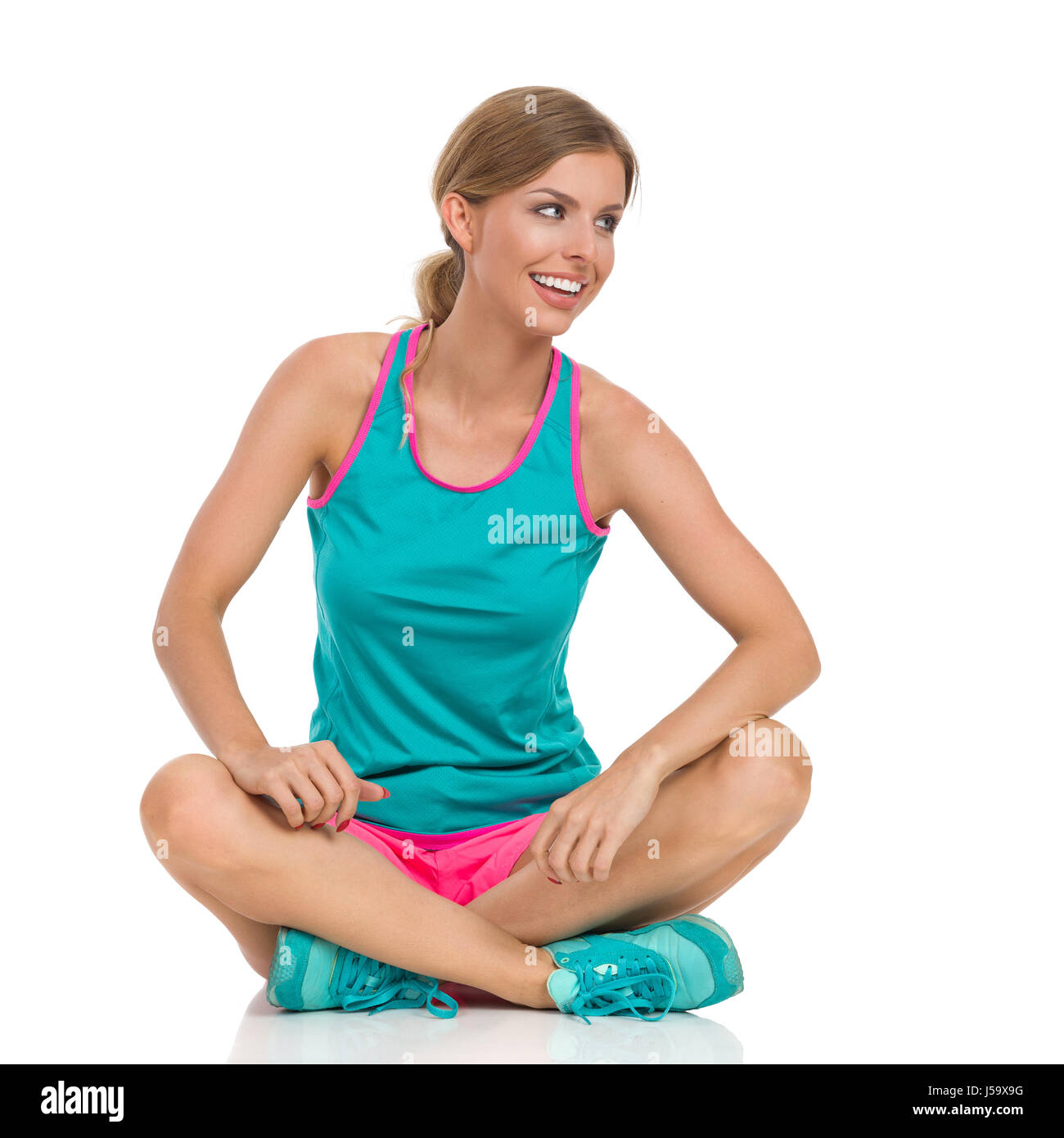 Beautiful smiling young woman in pink shorts, green tank top and sneakers sitting on a floor with legs crossed and - Stock Image