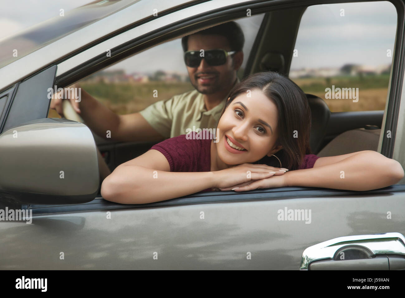 Young woman relaxing on car door during car ride Stock Photo