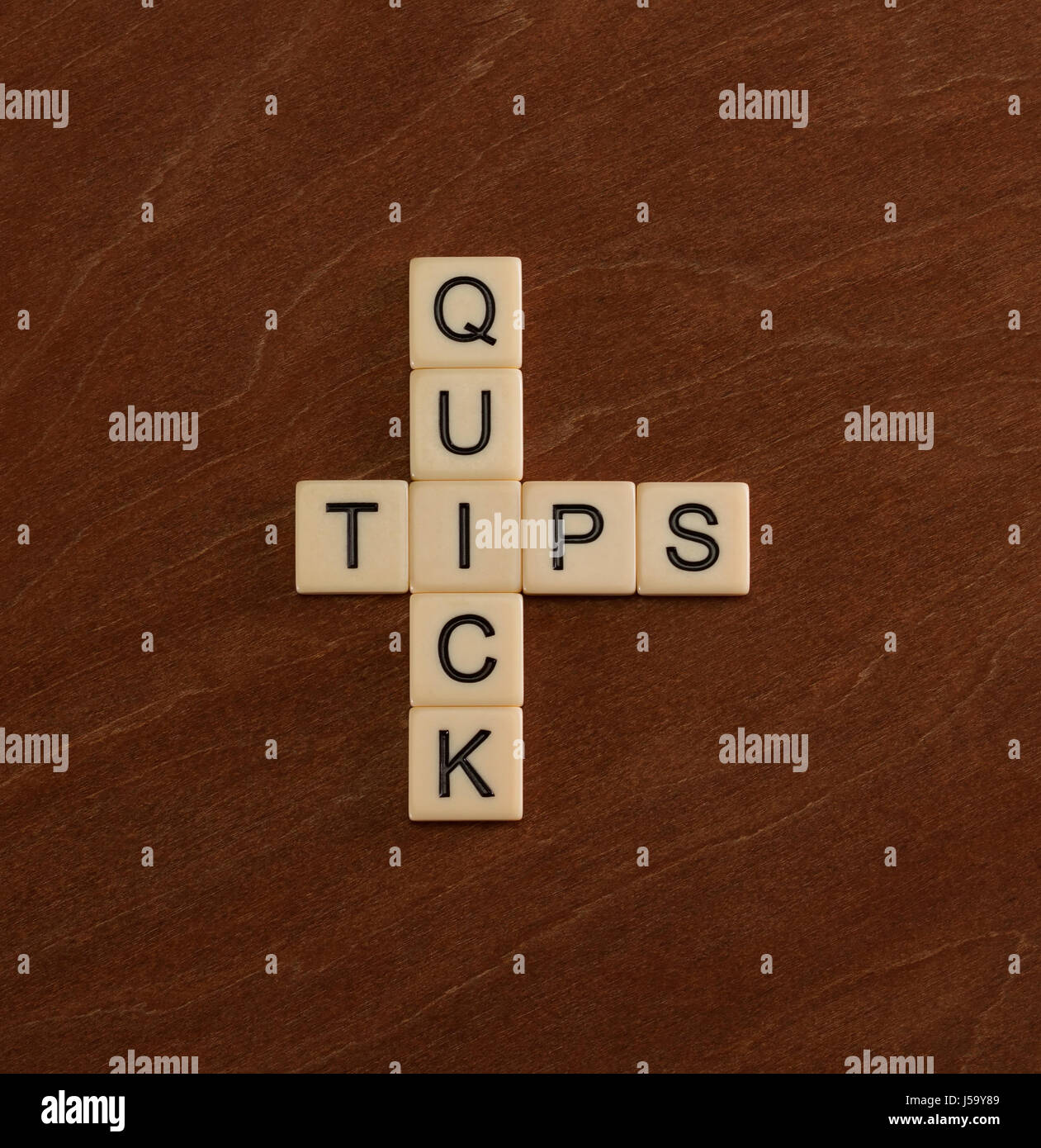 Crossword puzzle with words Quick Tips. Travel guide concept. Ivory tiles with capital letters on mahogany board. - Stock Image