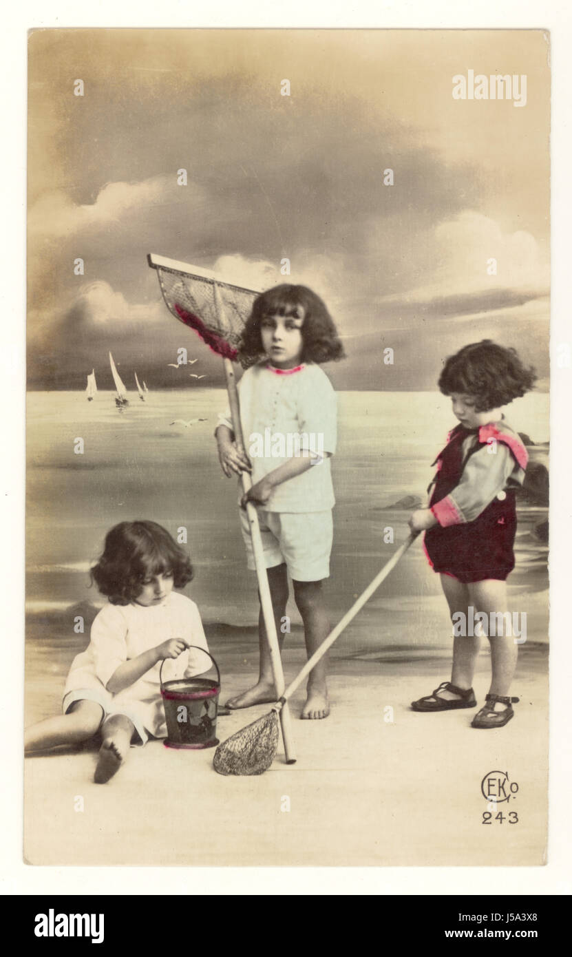 Early 1900's tinted French postcard of cute children with fishing nets with a beach backdrop set up in a photographic - Stock Image