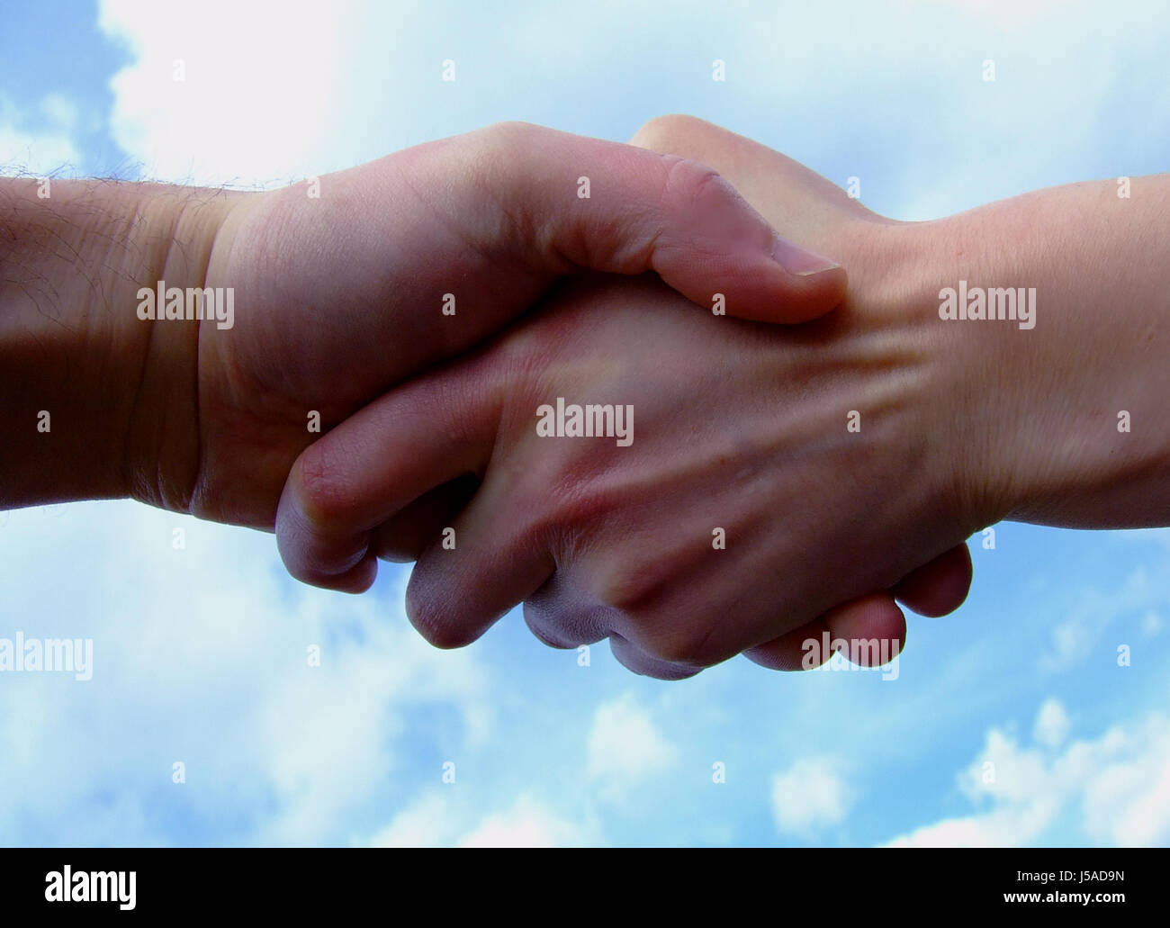 private blue hand hands friendship reach handshake contract arrangement - Stock Image