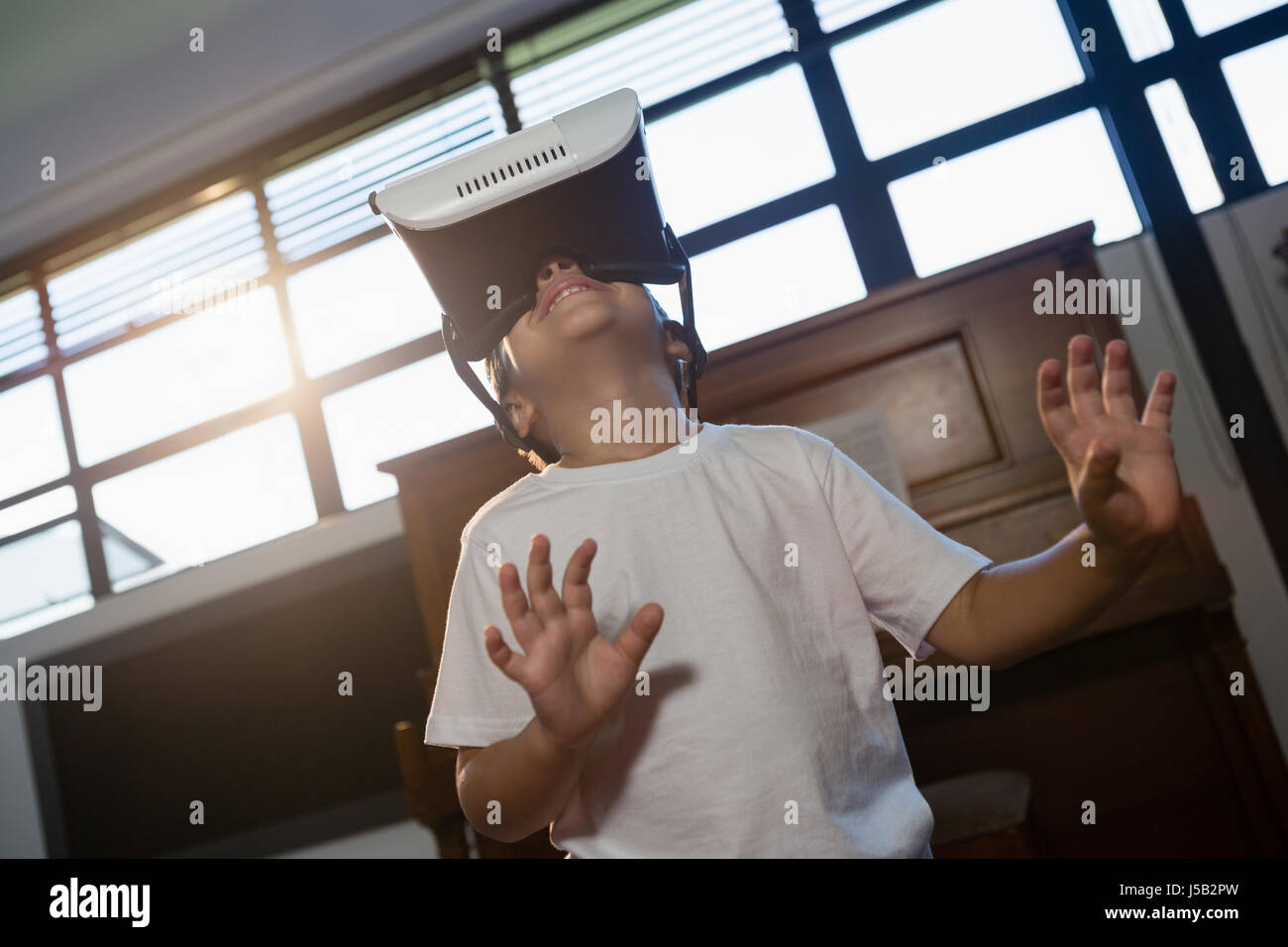 Low angle view of boy wearing virtual reality simulator gesturing while standing at home - Stock Image