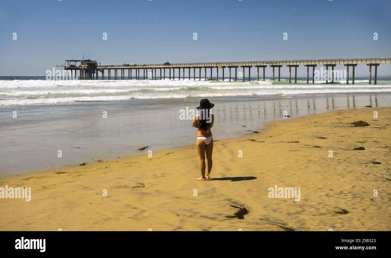 Lonely Woman in Trendy Hat on La Jolla Shores looking towards Scripps Pier - Stock Image