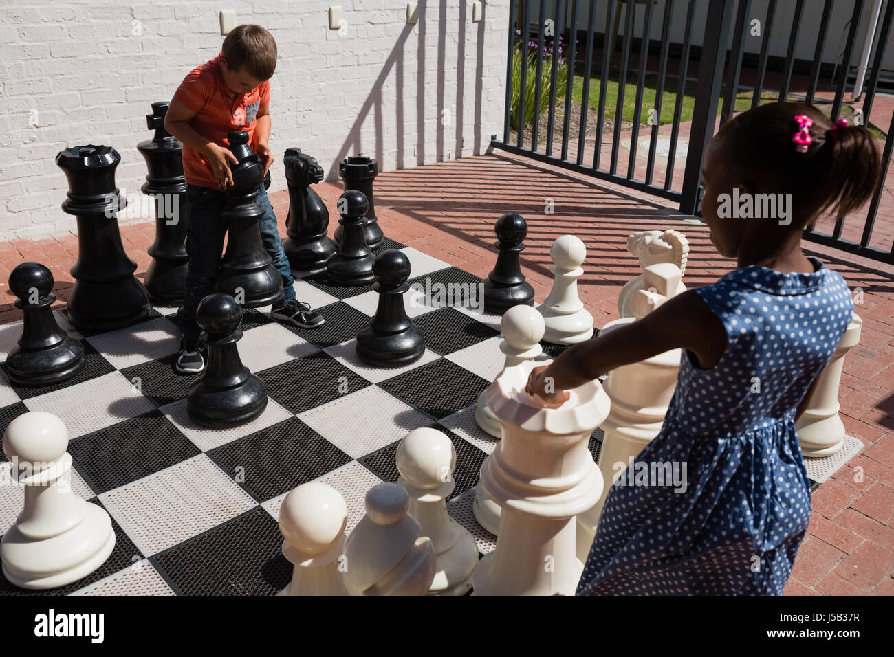 Classmates playing with large chess at school on sunny day Stock Photo