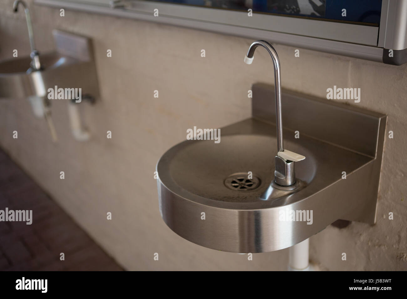 High angle view of drinking water faucet on sink at school Stock Photo